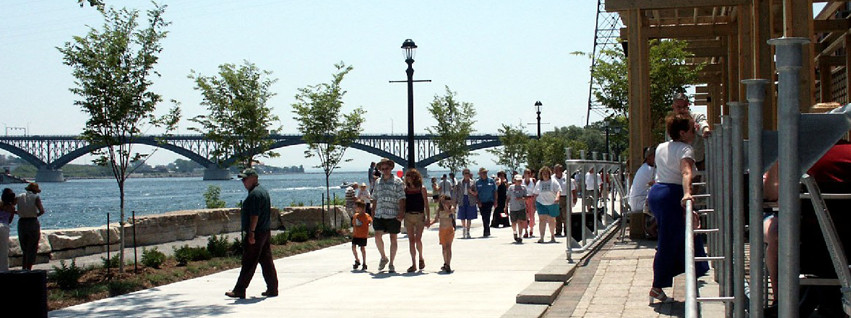 People walkin along the waterfront of the Niagara River with the Peace Bridge in the background